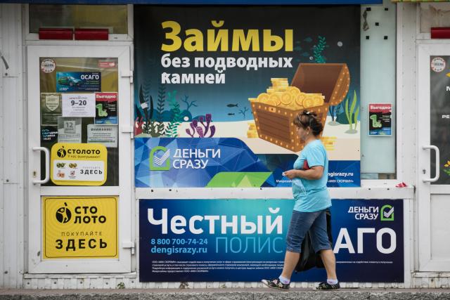 Женщина у офиса займов. Фото: Михаил Жбанков/ТАСС
