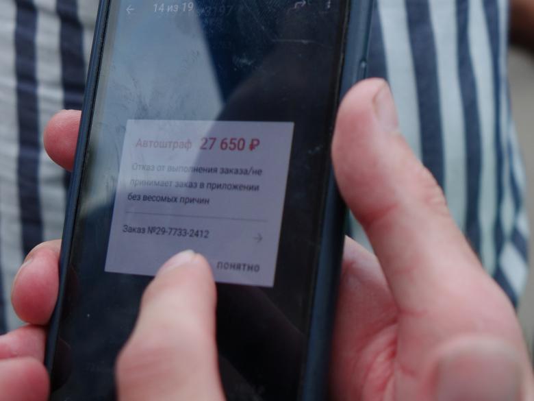 Уведомление о штрафе на экране смартфона бастующего курьера