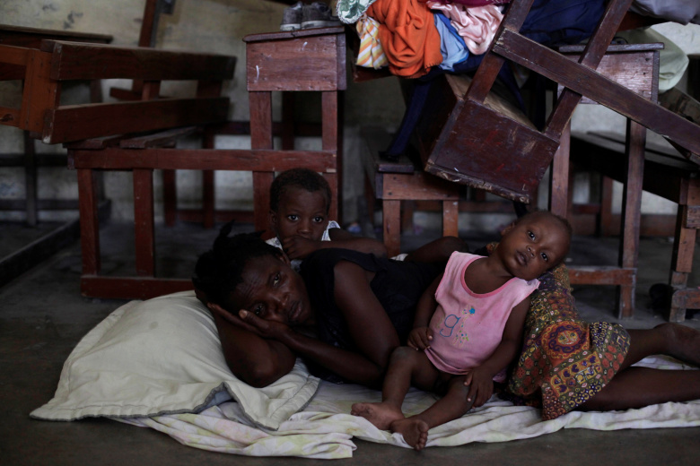 Женщина с двумя детьми укрывается в школе от надвигающегося урагана в городе Ле-Ке